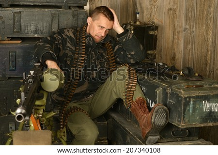 Thoughtful armed soldier sits among munitions close-up - stock photo
