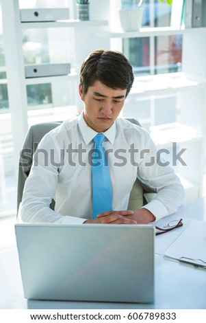 Thoughtful asian businessman at his desk in office