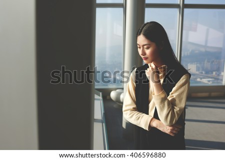 Thoughtful Asian female is pondering while look down on the city from last top floor of skyscraper building.Chinese business woman is thinking about her future career in information technology company