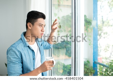 Thoughtful asian man looking out the window in bedroom at home