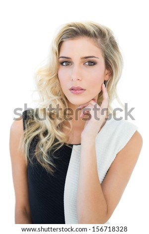 Thoughtful attractive blonde model looking at camera on white background - stock photo
