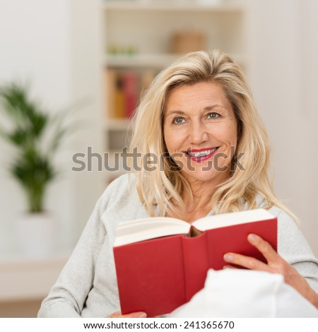Thoughtful attractive middle-aged woman sitting reading a book looking up into the air with a smile as she contemplates what she has just read - stock photo