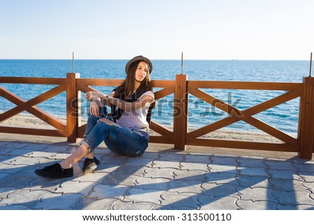 Thoughtful attractive woman dressed in stylish clothes enjoying good sunny weather during promenade, gorgeous hipster girl rest outdoors while strolling along the seashore in spring season - stock photo