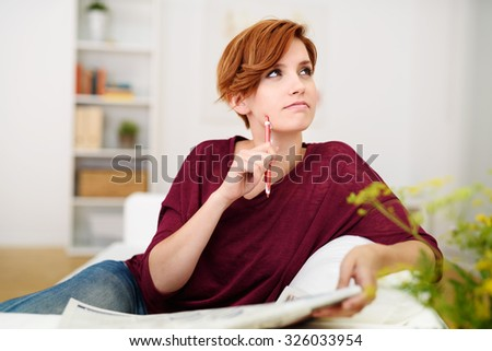 Thoughtful Attractive Young Woman Answering Crossword Puzzle Game on Newspaper at the Living Room Couch. - stock photo