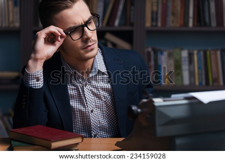 Thoughtful author. Thoughtful young author working at the typewriter and adjusting his eyeglasses while sitting at his working place with bookshelf in the background  - stock photo