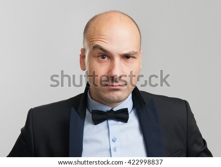 thoughtful bald business man with a raised eyebrow