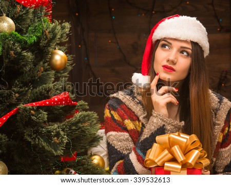 Thoughtful beautiful girl holding a present and dreaminf about surprise near New Year tree. Pretty lady in Santa hat looking away.