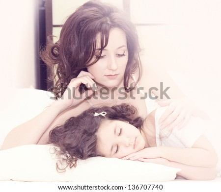 Thoughtful beautiful mother with her little daughter