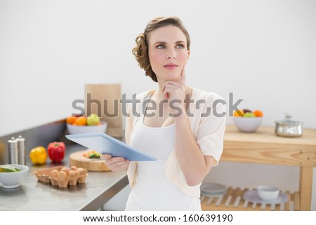 Thoughtful beautiful woman holding her tablet while standing in her kitchen at home - stock photo