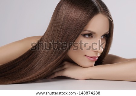 Thoughtful beauty. Attractive young women with beautiful hair looking at away while isolated on grey - stock photo