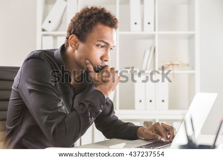 Thoughtful black businessman working on project on office desk with laptop and notepad. Bookshelf with documents in the background - stock photo