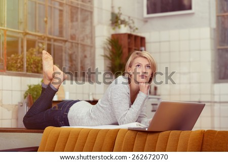 Thoughtful Blond Woman Lying on her Stomach on the Table Behind the Sofa with Legs Up and Fist on the Chin While Looking Up In Front of her Laptop Computer. - stock photo