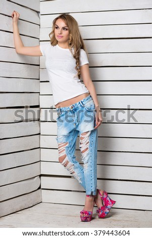 Thoughtful blond woman posing in blue ripped jeans and white t-shirt near wooden wall - stock photo