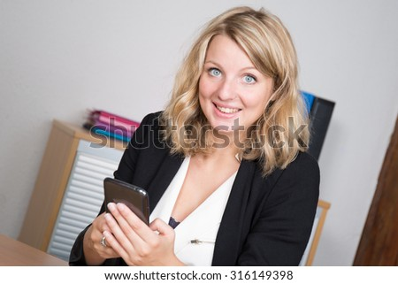 Thoughtful blonde businesswoman in bright office texting