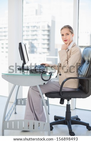 Thoughtful blonde businesswoman posing in bright office