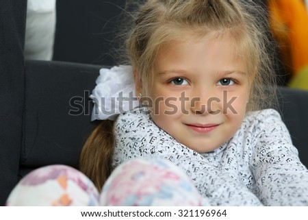 Thoughtful blonde little girl sitting on floor near couch portrait. Cute shy pensive female child looking in camera idling. Kid with serious face thinking and dreaming. Family concept - stock photo