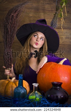 thoughtful blonde witch with a broom and pumpkins for Halloween