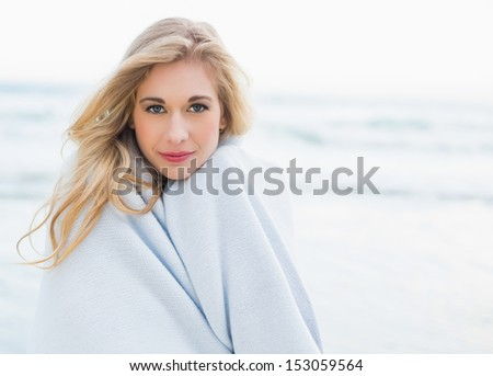 Thoughtful blonde woman covering herself in a blanket on the beach - stock photo
