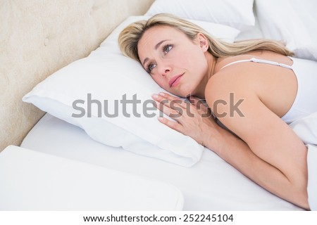 Thoughtful blonde woman lying in bed at home in the bedroom