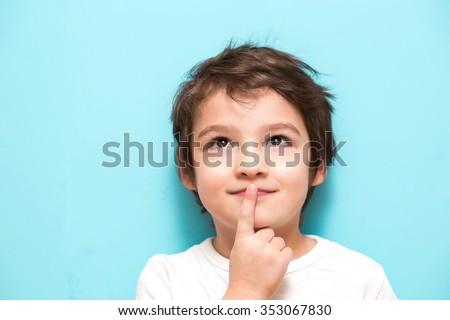Thoughtful boy brunette on a blue background - stock photo