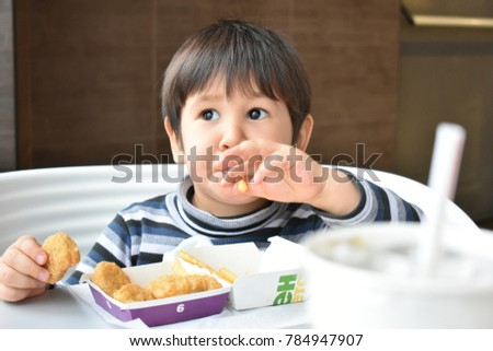Thoughtful boy eating nuggets and fries in the cafe
