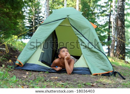 thoughtful boy in forest camping tent - stock photo