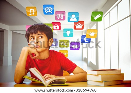 Thoughtful boy reading book in library against computing application icons - stock photo