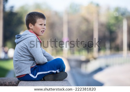 Thoughtful boy sitting on the edge of the granite plate, looks into the distance - stock photo