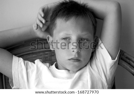 Thoughtful boy with serious expression. Closeup headshot, black and white photo - stock photo