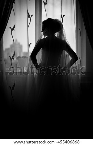 Thoughtful bride stands in the front of a window