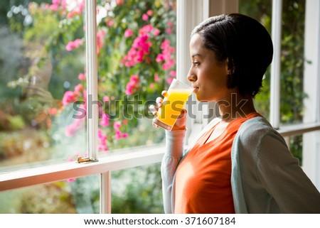 Thoughtful brunette drinking orange juice near the window - stock photo
