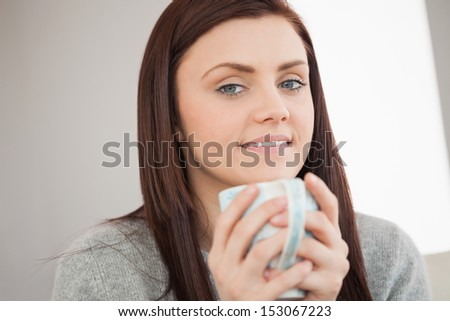 Thoughtful brunette holding a cup of coffee and looking at camera in a living room