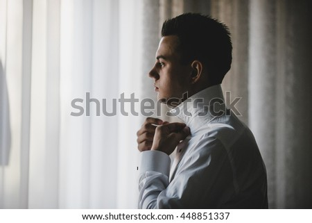 Thoughtful brunette man looks through the window buttoning up his shirt