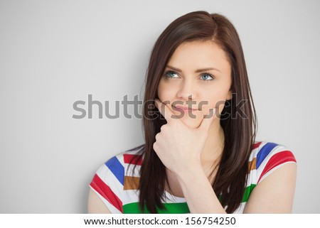 Thoughtful brunette posing and looking away on grey background - stock photo