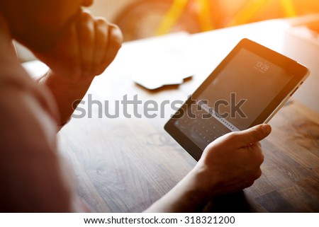 Thoughtful business man looking to the digital tablet screen while sitting in modern loft interior at wooden table,entrepreneur or freelancer work on touchscreen pad at the office,flare sun and filter - stock photo