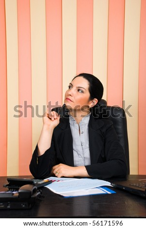 Thoughtful business woman  sitting on chair at desktop in office ,holding a pencil to chin and looking away