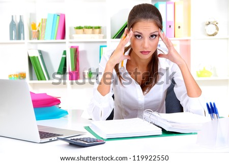 Thoughtful business woman with notebook in office - stock photo
