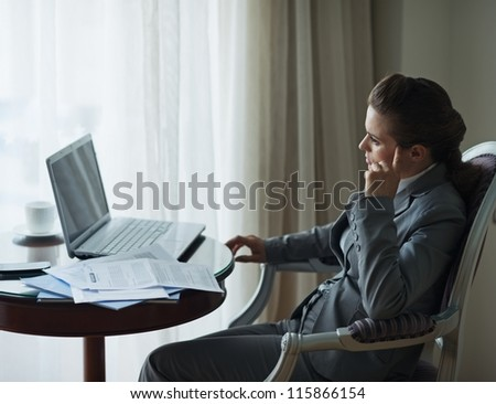Thoughtful business woman working at desk in hotel room