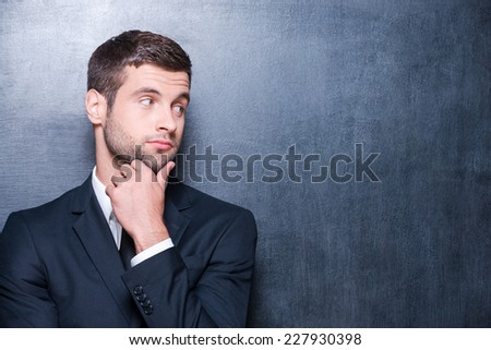 Thoughtful businessman. Handsome young man in shirt and tie holding hand on chin while standing against blackboard  - stock photo