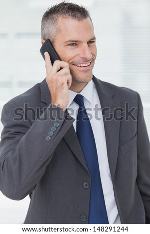 Thoughtful businessman in bright office posing while having a phone call - stock photo