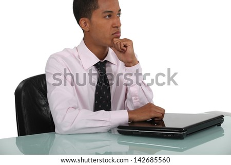 Thoughtful businessman leaning on a closed laptop - stock photo