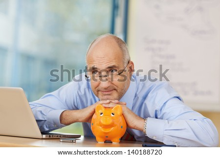 Thoughtful businessman leaning on piggy bank while looking away at office desk - stock photo