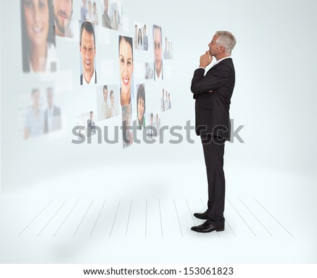 Thoughtful businessman looking at a wall covered by profile pictures on white background
