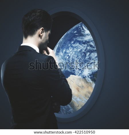 Thoughtful businessman looking at earth outside dark spaceship window. Elements of this image furnished by NASA. - stock photo