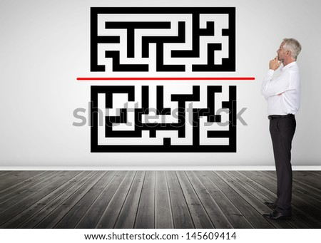 Thoughtful businessman looking at qr code on a wall - stock photo