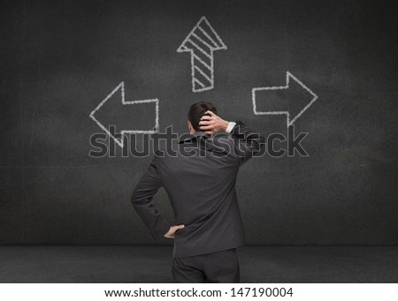 Thoughtful businessman looking at three arrows drawn on chalkboard - stock photo