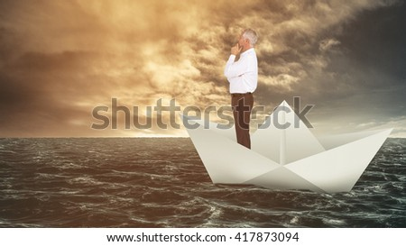 Thoughtful businessman posing against paper boat floating on the sea