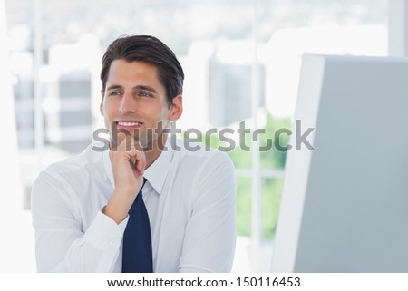 Thoughtful businessman posing looking away in his office