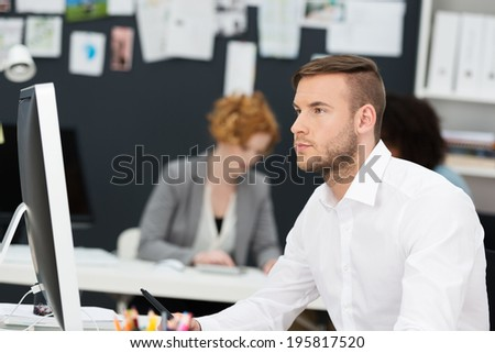 Thoughtful businessman reading information on his desktop computer screen concentrating as he digests the facts - stock photo