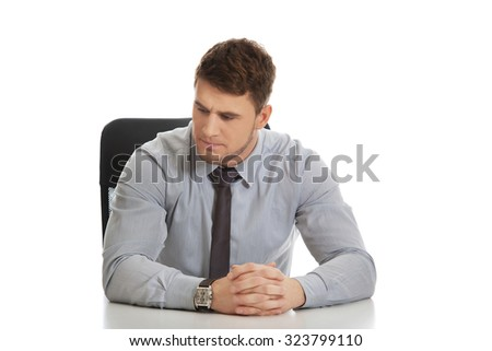 Thoughtful businessman sitting by a desk in the office.